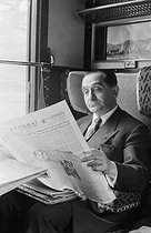 "Pierre Mendès France (1907-1982), French politician, reading the ""Combat"" newspaper in a train to Brittany, during the election campaign of the Republican Front. France, 1955. Photograph by Jean Marquis (1926-2019). © Jean Marquis / Roger-Viollet"