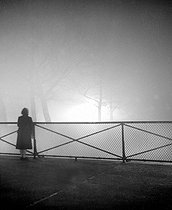 Woman standing on the pont des Arts, in the fog, at night. Paris (VIth arrondissement), January 1949. © Roger-Viollet