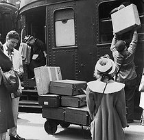 Porter unloading the travelers' luggage on the platform of a train station. © Roger-Viollet