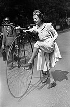 Young woman wearing capri pants with a penny-farthing. France. © LAPI / Roger-Viollet
