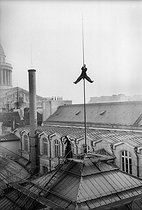 Henri Roger (1869-1946), French photographer, climbing the lightning conductor on the roof of the Paris Faculty of Law, on December 10, 1899. © Henri Roger / Roger-Viollet