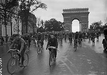 The cyclists of the Tour de France going down the avenue des Champs-Elysées on their bicycles before taking the train at the gare de Lyon to Evian where the start is to be given. Paris, 1926. © Maurice-Louis Branger/Roger-Viollet