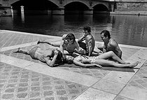 Tanning on the banks of the river Seine. Paris, July 1952. © Roger-Viollet
