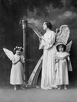 Angel playing the harp with two cherubs. Fancy postcard, circa 1910. © Neurdein/Roger-Viollet