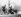 Guerre 1939-1945. Bataille des Ardennes. Soldats SS de l'armée allemande passant devant un char de l'armée américaine en feu, vers le 20 décembre 1944. © Ullstein Bild / Roger-Viollet