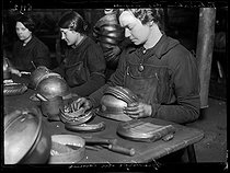 "World War One. Workers of a French helmet manufacture, typical war industry. Adjusting of the crests. Photograph published in the newspaper ""Excelsior"", on January 29, 1916. © Wackernie/Excelsior – L'Equipe/Roger-Viollet"