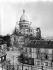 La place du Tertre et la basilique du Sacré-Coeur de Montmartre avec la tour en construction. Paris (XVIIIème arr.), vers 1910. © Léon et Lévy / Roger-Viollet