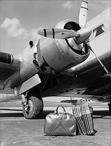 "Advertisement for ""Trois Quartiers"" luggage in front of a Bloch M.B.220 plane of Air France. Le Bourget (France), 1939. © Pierre Jahan / Roger-Viollet"