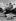 """Publicité pour des bagages """"Trois Quartiers"""" devant un avion Bloch M.B. 220 d'Air France. Le Bourget (Seine-Saint-Denis), 1939. © Pierre Jahan / Roger-Viollet"""