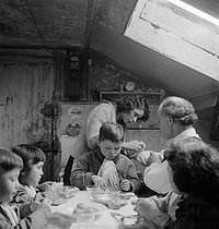 Large family during dinner. Paris (France), about 1956. © Janine Niepce/Roger-Viollet