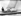 """Le prince Charles avec son père, le prince Philip, et les membres d'équipage: Uffa Fox, conseiller du duc d'Edimbourg et second, et Alistair Easton, capitaine du voilier """"Bluebottle"""", pendant la course de voiliers de la classe des Dragons. Cowes (Ile de Wight, Angleterre), 6 août 1957. © PA Archive/Roger-Viollet"""