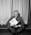 """Jean Cocteau (1889-1963), French writer, posing with the cover of his last film, """"Le testament d'Orphée, ou ne me demandez pas pourquoi !"""", 1960. © Claude Poirier / Roger-Viollet"""