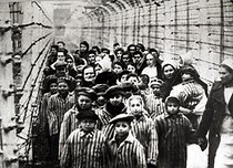 World War II. Jewish children survivors of Auschwitz With nurse behind barbed wire fence. Photo taken by Russian photographerduring making of a film about liberation of the camp.Children were dressed up by the Russians with clothing from adult prisoners. Auschwitz (Poland), February 1945. Galerie Bilderwelt.        BIL-AU 03 © Bilderwelt / Roger-Viollet