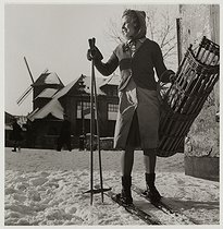 World War II. Young girl carrying bread on skis, windmill in a snowy street, Montmartre, Paris (XVIIIth arrondissement). 1941. Photograph by Roger Schall (1904-1995). Paris, musée Carnavalet.  © Roger Schall/Musée Carnavalet/Roger-Viollet