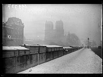 "The quai des Grands-Augustins and the Notre-Dame de Paris Cathedral, under the snow. Paris (VIth arrondissement), December 1938. Photograph from the collections of the French newspaper ""Excelsior"". © Excelsior - L'Equipe / Roger-Viollet"