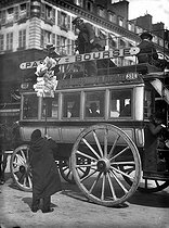 Newspaper seller in front of a double-decker. Paris,1899.  © Jacques Boyer/Roger-Viollet