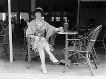 Woman at the terrace of a café, on the wooden boardwalk (Planches) of Deauville (France), 1925-1930. © Maurice-Louis Branger / Roger-Viollet