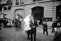 "Events of May-June 1968. Demonstration of ""Occident"" (French far-right militant political group), in front of the headquarters of the newspaper ""Humanité"", rue Réaumur. A demonstrator burning the newspaper front page. Paris (IInd arrondissement), on May 21st, 1968. Photograph by Claude Champinot, from the collections of the French newspaper ""France-Soir"". Bibliothèque historique de la Ville de Paris.   © Claude Champinot / Fonds France-Soir / BHVP / Roger-Viollet"