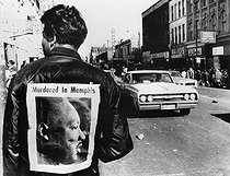 ML King assassination. Personalities. Mono Negative. A man wears a placard proclaiming the death of Dr. Martin Luther King - cut from a local newspaper - as he watches looters stealing from stores in the background as violence, looting and fireraising flared on 5th April 1968 after the slaying of the negro leader.Chicago. 19680405. © TopFoto / Roger-Viollet