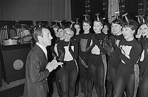 """Charles Aznavour (1924-2018), Armenian-born French singer-songwriter and actor, with the dancers from the """"Music Hall de Moscou"""" show. Paris, Olympia, 1964. Photograph by André Grassart (born in 1935), from the collections of the newspaper """"France-Soir"""". Bibliothèque historique de la Ville de Paris. © André Grassart / BHVP / Roger-Viollet"""