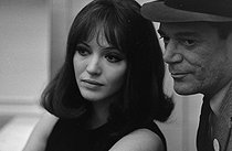 "Anna Karina (1940-2019), Danish-born French actress, singer and writer, with Edddie Constantine (1913-1993), American singer and actor, during the shooting of ""Alphaville, une étrange aventure de Lemmy Caution"", film by Jean-Luc Godard, January 1965. Photograph by André Grassart (born in 1935), from the collections of the French newspaper ""France-Soir"". Bibliothèque historique de la Ville de Paris. © André Grassart / BHVP / Roger-Viollet"