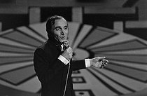 """Charles Aznavour (1924-2018), Armenian-born French singer-songwriter and actor, performing in """"Le Palmarès des chansons"""", television program hosted by Guy Lux and Anne-Marie Peysson, on January 4, 1968. Photograph by Bernard Hermann (born in 1941), from the collections of the newspaper """"France-Soir"""". Bibliothèque historique de la Ville de Paris. © Bernard Hermann / BHVP / Roger-Viollet"""