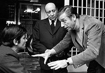 """Alain Delon (born in 1935), French actor, Jean-Pierre Melville (1917-1973), French film-maker and actor, and Yves Montand (1921-1991), French-Italian actor. Shooting of the film """"Le Cercle Rouge"""" (The Red Circle), by Jean-Pierre Melville. Boulogne Billancourt (Hauts-de-Seine, France), 13 February 1970. © André Perlstein / Roger-Viollet"""