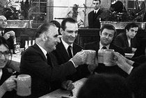 """Georges Pompidou (1911-1974), Prime Minister and candidate for the French presidential elections, and Jacques Chirac (1932-2019), Secretary of State, drinking some beers in the Alsatian tavern """"L'ours blanc"""", at the end of the Congrès UJP. Strasbourg (France), 12 April 1969. Photograph by André Perlstein (born in 1942). © André Perlstein / Roger-Viollet"""
