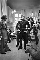 Yves Saint-Laurent (1936-2008), French fashion designer, costume designer and businessman, dressing Johnny Hallyday (1943-2017), French singer, for his concert at the Palais des sports, in his workshops at the Maison Saint-Laurent, avenue Montaigne, with on the left Pierre Bergé (1930-2017), French entrepreneur, and André Perlstein on the right. Paris (VIIIth arrondissement), 1977. Photograph by André Perlstein (born in 1942). © André Perlstein / Roger-Viollet