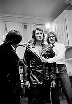"""Yves Saint-Laurent (1936-2008), French fashion designer, costume designer and businessman, dressing Johnny Hallyday (1943-2017), French singer, for his concert at the Palais des sports, in the workshops of the """"Maison Saint-Laurent"""", avenue Montaigne. Paris (VIIIth arrondissement), 1977. Photograph by André Perlstein (born in 1942). © André Perlstein / Roger-Viollet"""