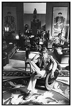 Yves Saint-Laurent (1936-2008), French fashion designer, costume designer and businessman, at his house, rue de Babylone, sitting in the middle of furniture and objects that were auctioned after his death, worth 375 millions d'euros for the Pierre Bergé foundation (1930-2017). Paris (VIIth arrondissement), 1977. Photograph by André Perlstein (born in 1942). © André Perlstein / Roger-Viollet