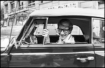 Yves Saint-Laurent (1936-2008), French fashion designer, at the wheel of his car, a convertible Coccinelle Volkswagen. Paris, 1977. Photograph by André Perlstein (born in 1942). © André Perlstein / Roger-Viollet