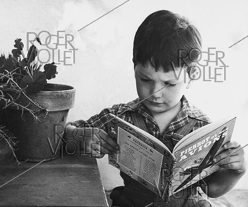 Roger-Viollet | 794192 | 4-year old boy reading a comic book. France, 1950. Photograph by Janine Niepce (1921-2007). | © Janine Niepce / Roger-Viollet