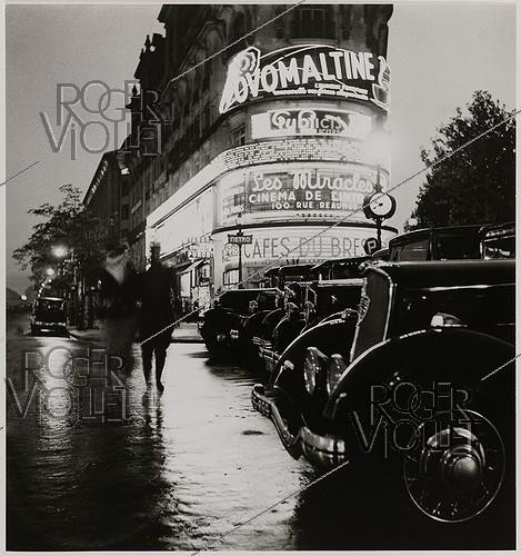 Roger-Viollet | 362656 | Advertising neon signs at the Richelieu-Drouot crossroads with cars and metro entrance. Paris (IXth arrondissement). 1935. Photograph by Roger Schall (1904-1995). Paris, musée Carnavalet. | © Roger Schall / Musée Carnavalet / Roger-Viollet