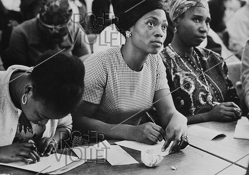 Roger-Viollet | 605841 | African immigrant women. Writing lesson by the charity  Union Féminine Civique et Sociale . Photograph by Janine Niepce (1921-2007). | © Janine Niepce / Roger-Viollet