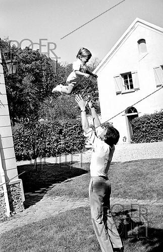 Roger-Viollet | 833942 | Alain Delon (born in 1935), French actor, with his son Anthony for his christening, on May 1st, 1966. Photograph by Georges Kelaïditès (1932-2015). | © Georges Kelaïditès / Roger-Viollet