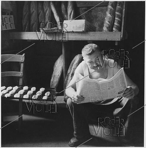 Roger-Viollet | 518543 | Baker reading the newspaper. Charente (France), 1959. Photograph by Janine Niepce (1921-2007). | © Janine Niepce / Roger-Viollet