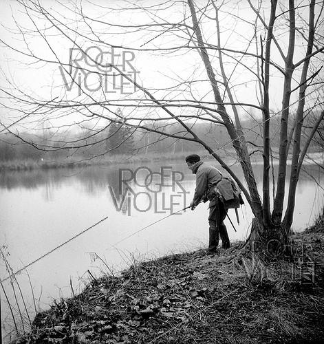 Roger-Viollet | 534097 | Bank fishing with light lures on a river bank. France, 1950's. | © Tony Burnand / Roger-Viollet