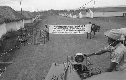 Roger-Viollet | 1031441 | Banner in a farm village, inciting workers to productivity gains. Cuba, around 1960. | © Gilberto Ante / Roger-Viollet