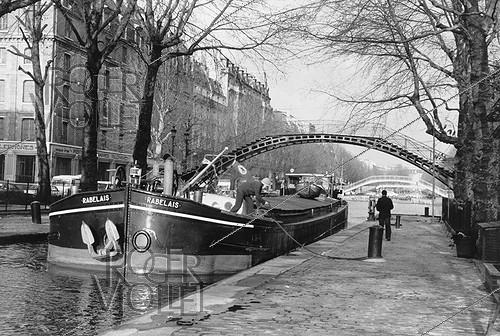 Roger-Viollet | 827884 | Barge on the Canal Saint-Martin, quai de Jemmapes. Paris, 1980's. Photograph by Janine Niepce (1921-2007). | © Janine Niepce / Roger-Viollet