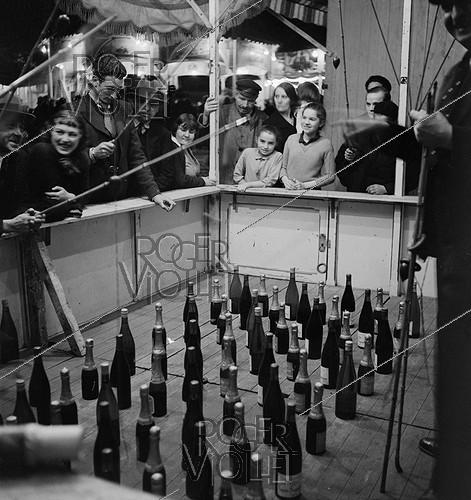 Roger-Viollet | 654884 | Bottle fishing in a fun fair. | © Gaston Paris / Roger-Viollet