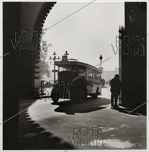 Roger-Viollet | 649688 | Bus driving under the arcade of the Louvre (palace and museum), Paris (Ist arrondissement). 1937. Photograph by Roger Schall (1904-1995). Paris, musée Carnavalet. | © Roger Schall / Musée Carnavalet / Roger-Viollet