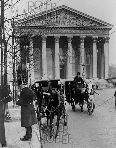 Roger-Viollet | 963580 | Cab station near the Madeleine church. Paris (VIIIth arrondissement), rue Royale, circa 1900. | © Roger-Viollet / Roger-Viollet
