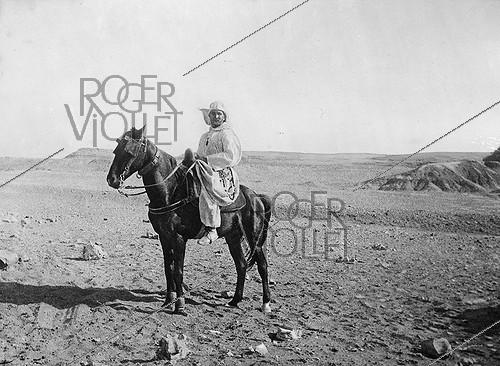 Roger-Viollet | 572059 | Charles de Foucauld (1858-1916), French explorer and monk, riding his horse in the desert. | © Albert Harlingue / Roger-Viollet