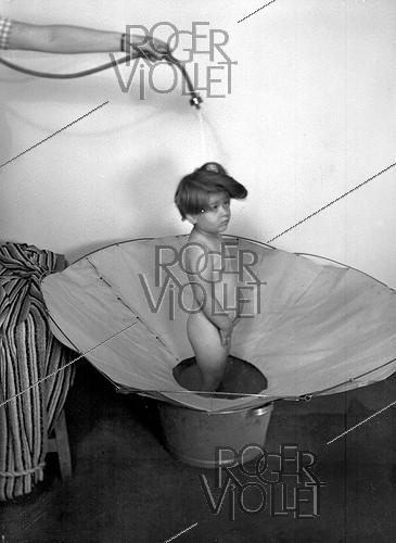 Roger-Viollet | 831116 | Child having a shower. Cloth device replacing the tub, 1946. | © Jacques Boyer / Roger-Viollet