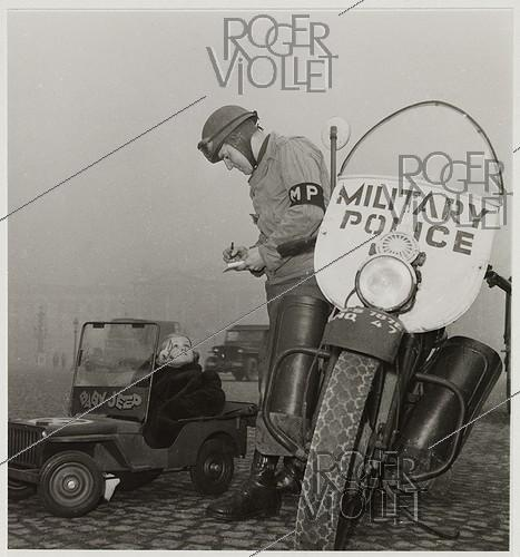 Roger-Viollet | 621873 | Child in a  baby jeep  pedal car giving the V-sign to a soldier of the Military Police, writing a fine, place de la Concorde, Paris (Ist and VIIIth arrondissements). 1945. Photograph by Roger Schall (1904-1995). Paris, musée Carnavalet. | © Roger Schall / Musée Carnavalet / Roger-Viollet
