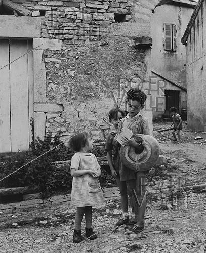 Roger-Viollet | 807150 | Children carrying some bread, crown-shaped or baguette. Rully (Saône-et-Loire), 1950. Photograph by Janine Niepce (1921-2007). | © Janine Niepce / Roger-Viollet