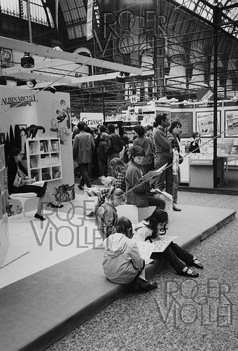 Roger-Viollet | 495027 | Children reading during a book fair at the Grand Palais. Paris (VIIIth arrondissement), April 1983. Photograph by Janine Niepce (1921-2007). | © Janine Niepce / Roger-Viollet