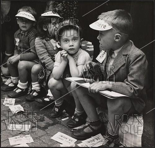 Roger-Viollet | 1078631 | Children wearing caps of the newspaper  La Vie Ouvrière . Leaflets announcing that the French politician Maurice Thorez is fine. Paris, 1950. Photograph by Janine Niepce (1921-2007). | © Janine Niepce / Roger-Viollet