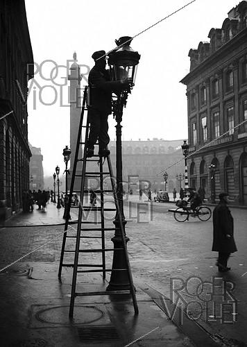 Roger-Viollet | 550688 | Cleaning street lamps on the place Vendôme. Paris (Ist arrondissement), 1944. | © LAPI / Roger-Viollet